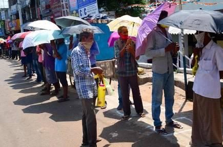 TeluguStop.com - గొడగులను క్యూలో పెట్టి.. కష్టాలు పడుతున్న మందుబాబులు-General-Telugu-Telugu Tollywood Photo Image